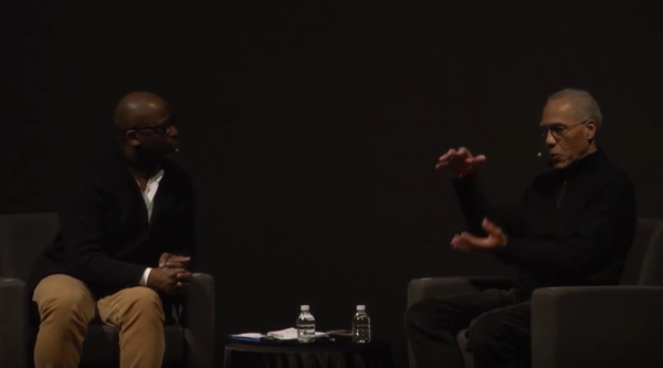 Two seated men, artists Theaster Gates and Martin Puryear, talk to each other on a stage