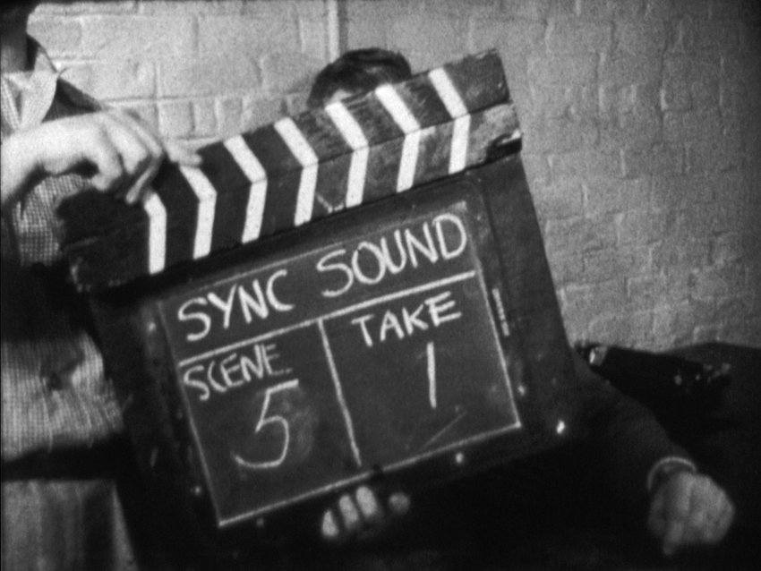 Black and white film still featuring a screen marker