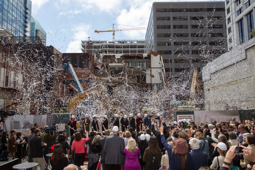 A crowd cheers and confetti flies as a line of people in suits and hard hats break ground at the SFMOMA construction site
