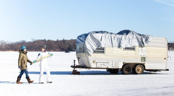 two people walking on snow covered field next to trailer