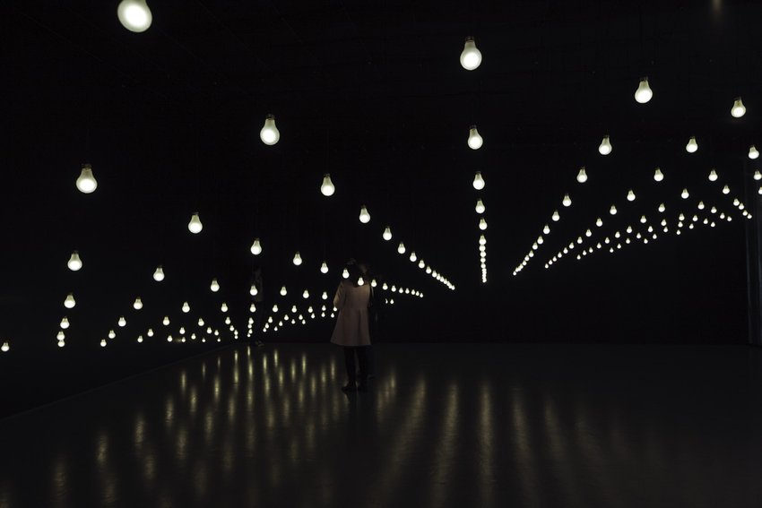 A visitor stands in a darkened room with white light bulbs running the length of the