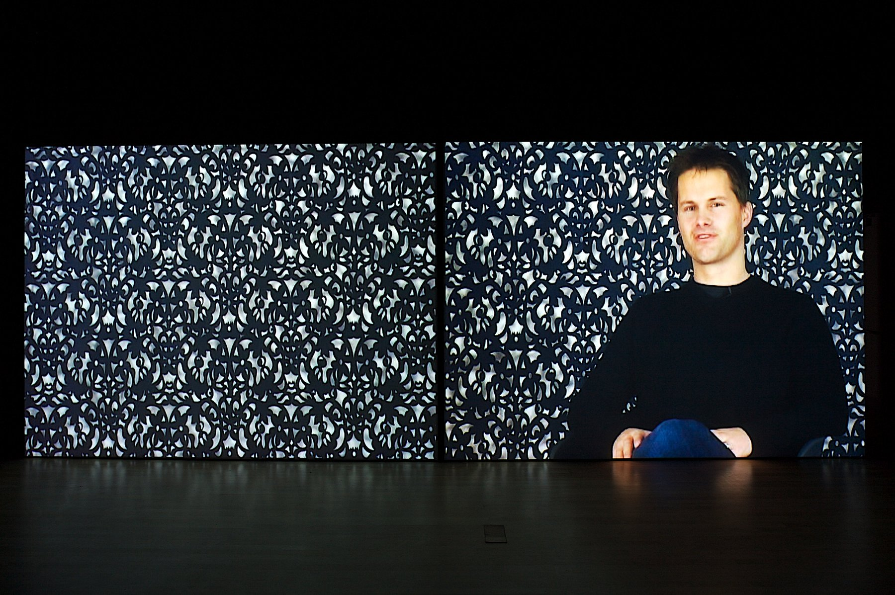 An image of a man sitting in front of a patterned wall.