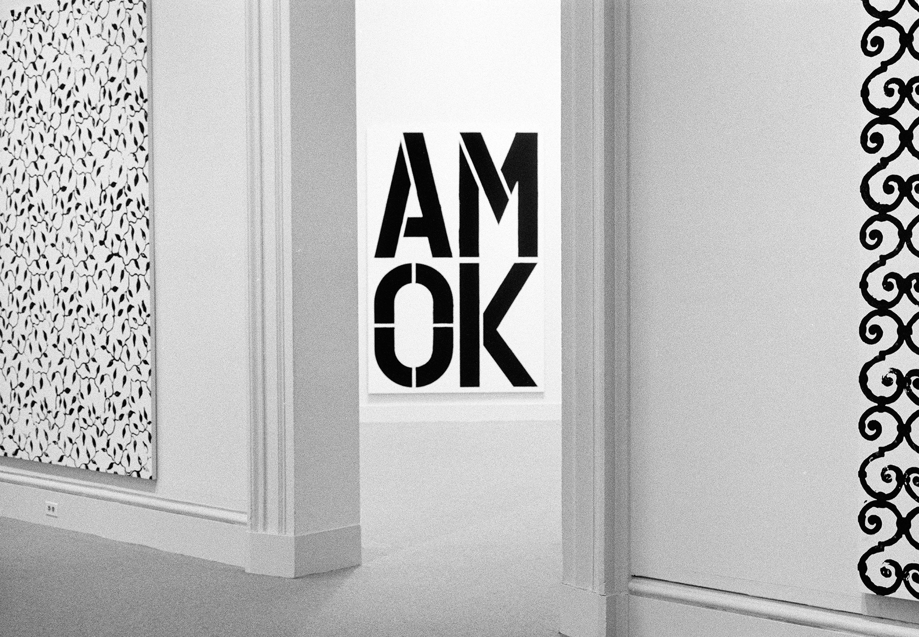 "A large black and white painting that reads ""AM OK"""