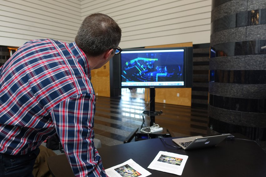 A man wearing a checkered shirt looks at a computer screen