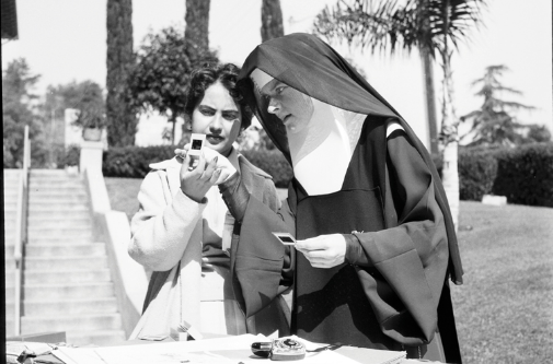 A nun wearing a habit stands outside with a young woman and examines a group of photographic slides in the sun