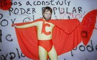 "A man in a caped yellow and red superhero costume emblazoned with the letter ""C"" stands in front of a wall spray painted with words in Spanish"