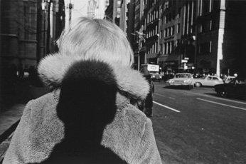 shadow of man's head on back of woman wearing fur coat