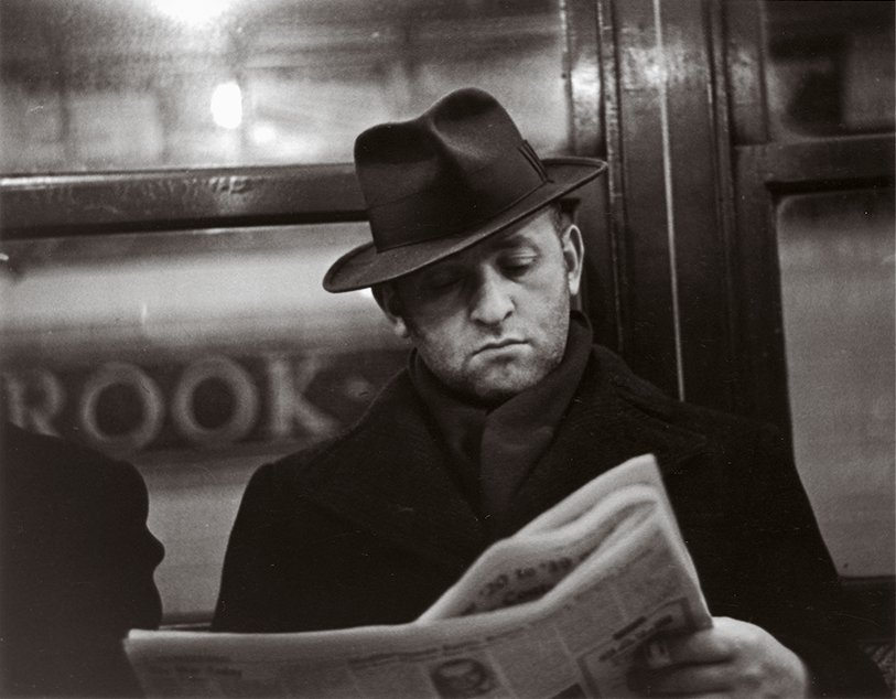 A black and white photography of a Caucasian man wearing a fedora reading a newspaper