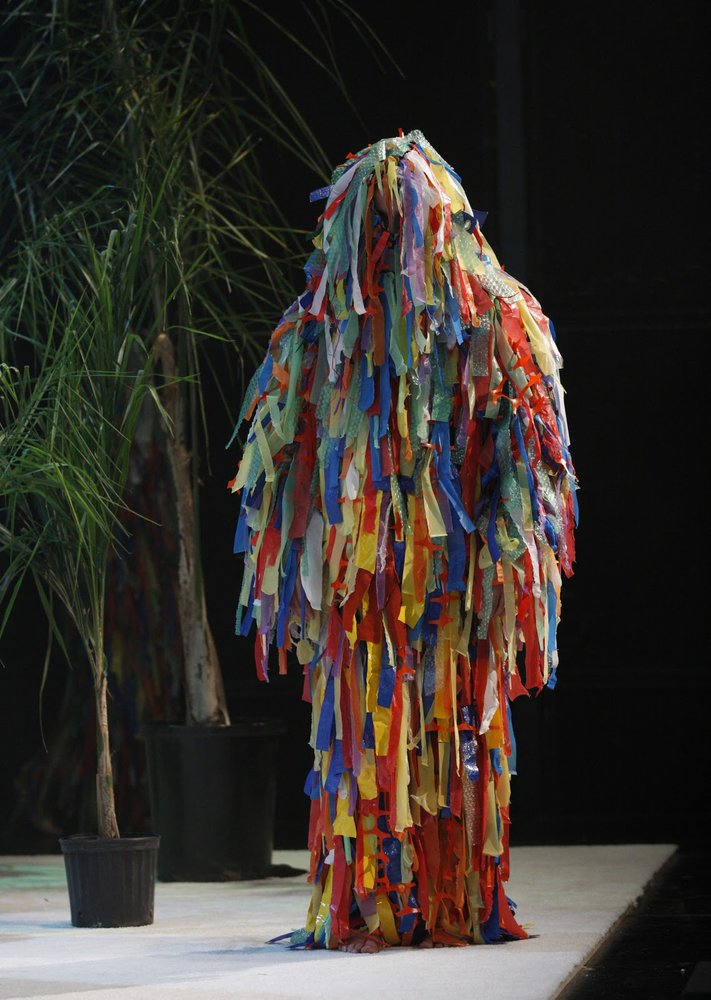 A figure wears a multi-colored ghillie suit