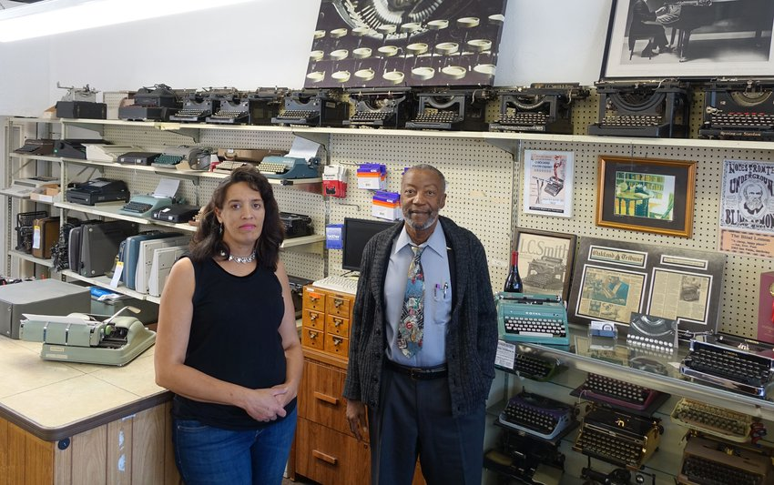 An African American man and woman stand before a wall filled with vintage typewriters