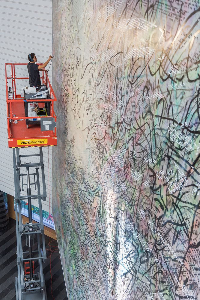 An African American woman stands on a scissor lift with an airbrush ready to paint an enormous canvas, Mehretu