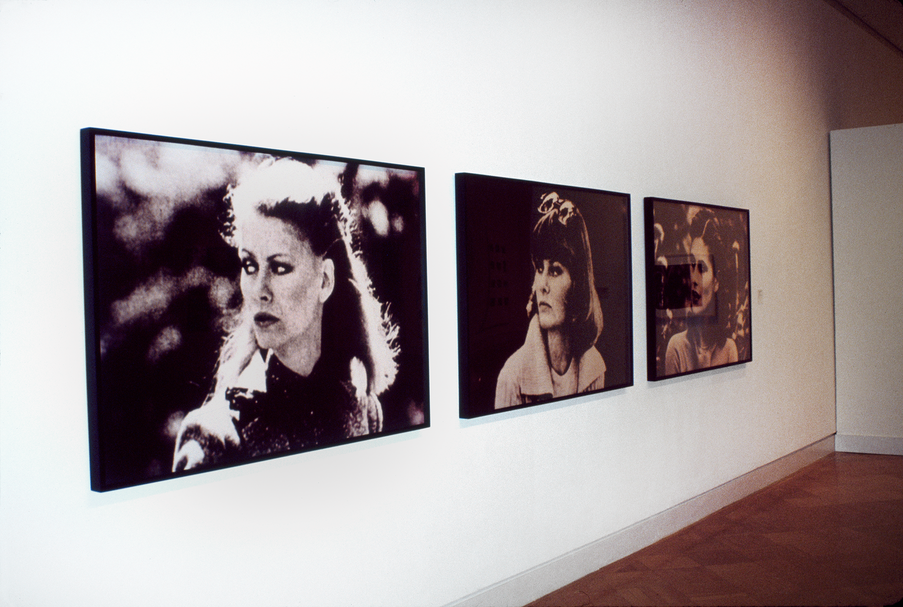 Three photographic portraits of women hung on a gallery wall