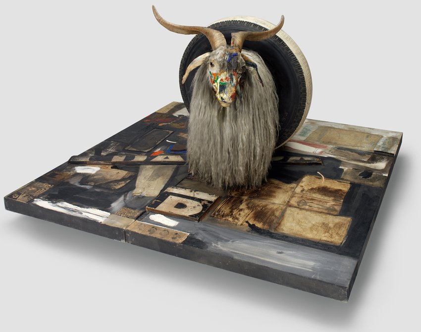 A colorfully painted Angora goat head ina rubber tire atop a wood platform