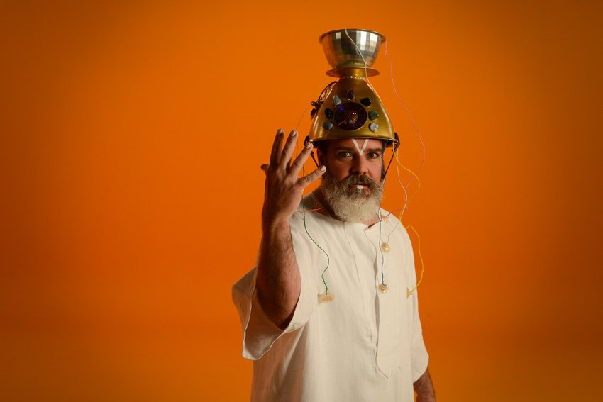 An elderly bearded man in front of an orange background wears a hat made of a colander and other recycled materials, Holman