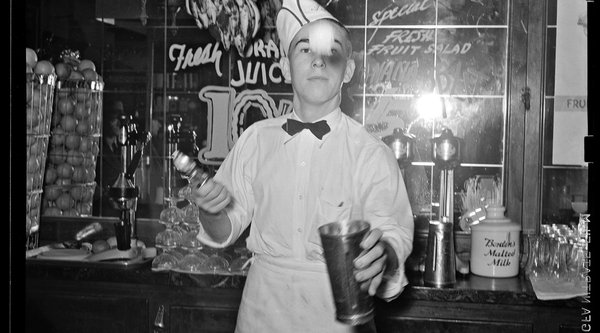 A black and white photograph of a soda fountain clerk
