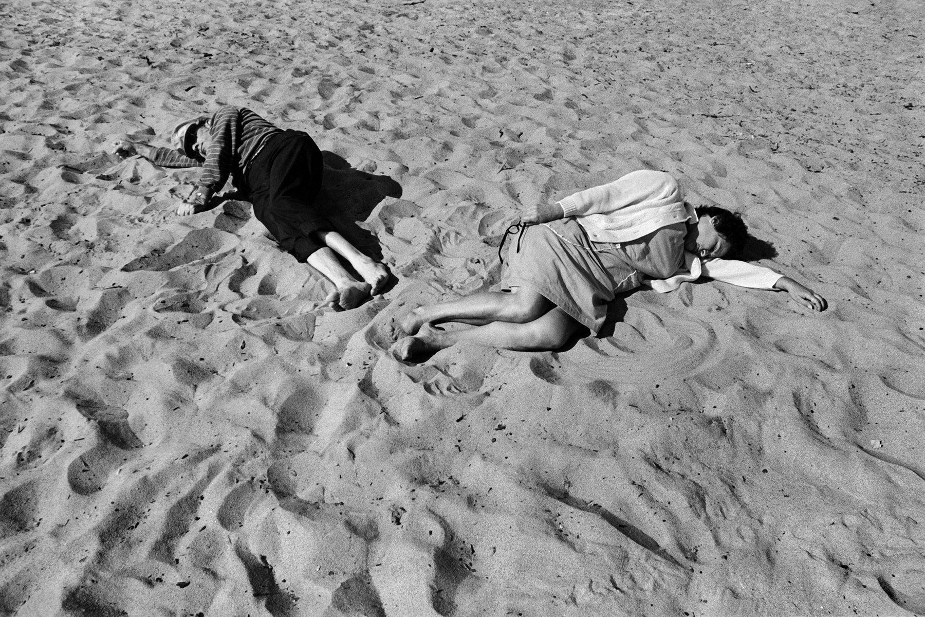 Two people lay in the sand
