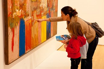 woman and young girl pointing and looking at painting
