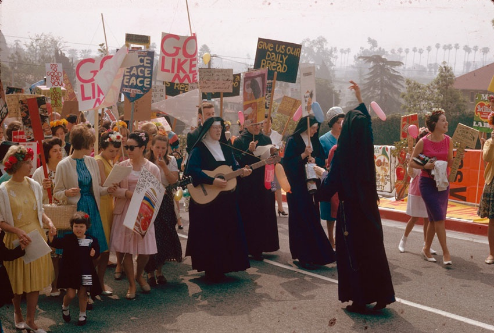 Several nuns in habits lead a group of young women carrying protest signs