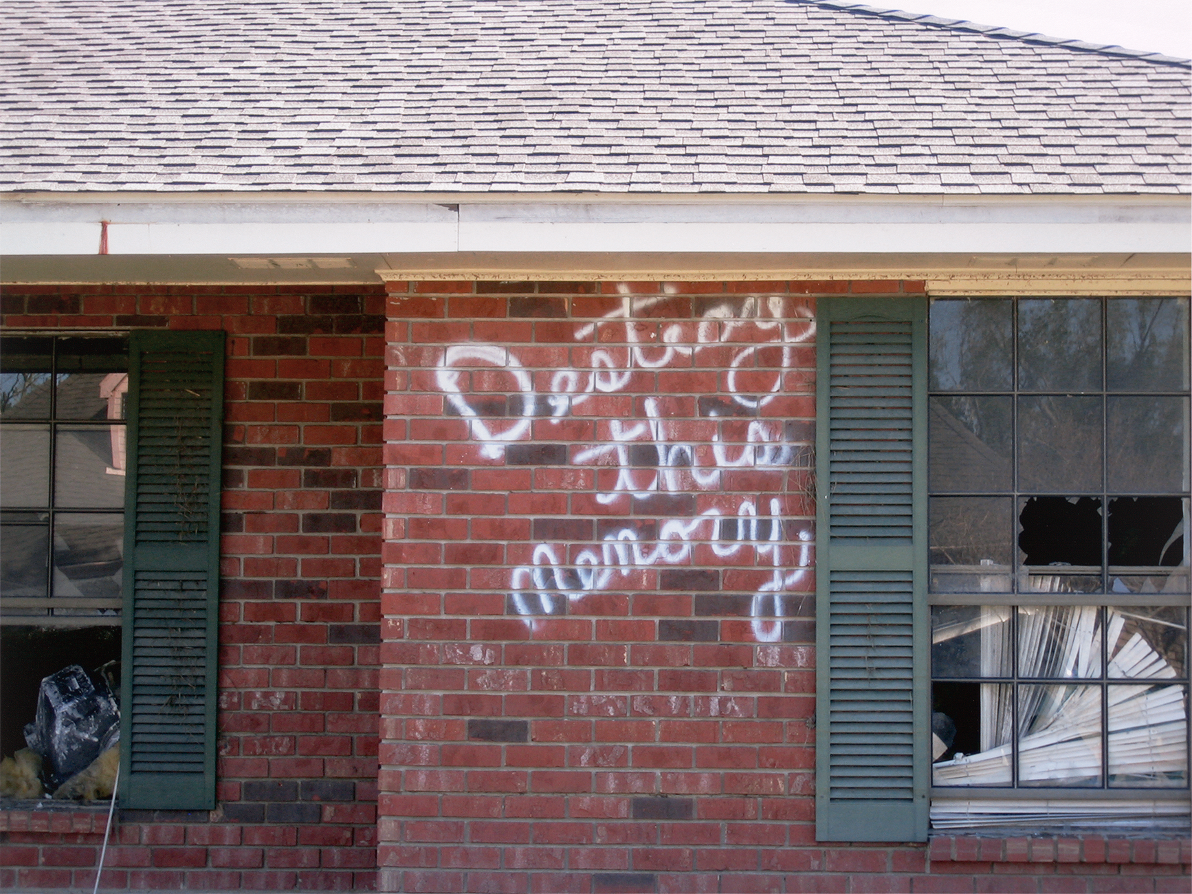 "A house with the words "" Destroy this memory"" spray-painted on the side"