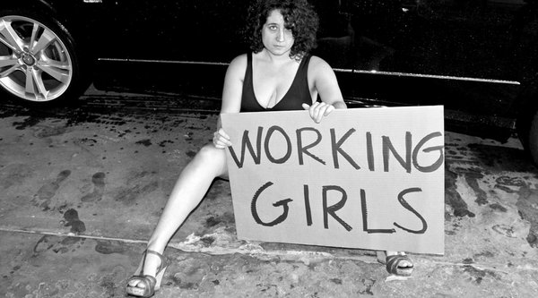 "A black and white photograph of a woman sitting on the street holding a cardboard sign that says ""working girls"""