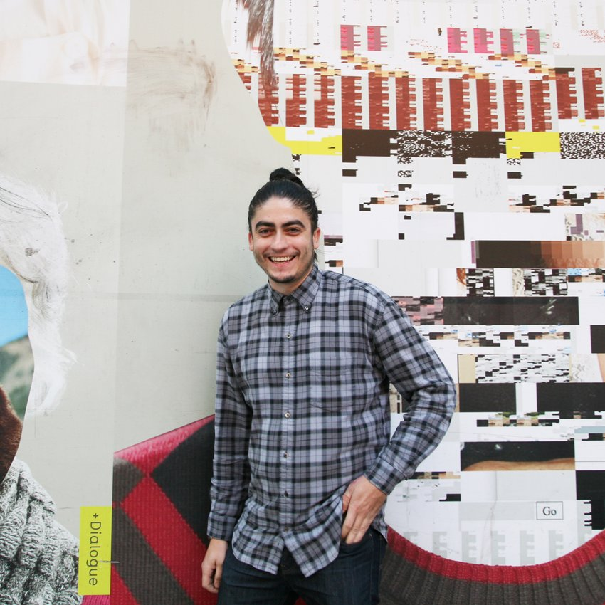 A smiling man stands in front of an abstract mural