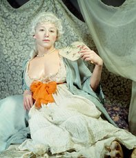 Cindy Sherman reclining in long dress and white wig