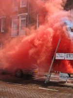 "Red smoke envelops a car and a sign that says ""Art"""