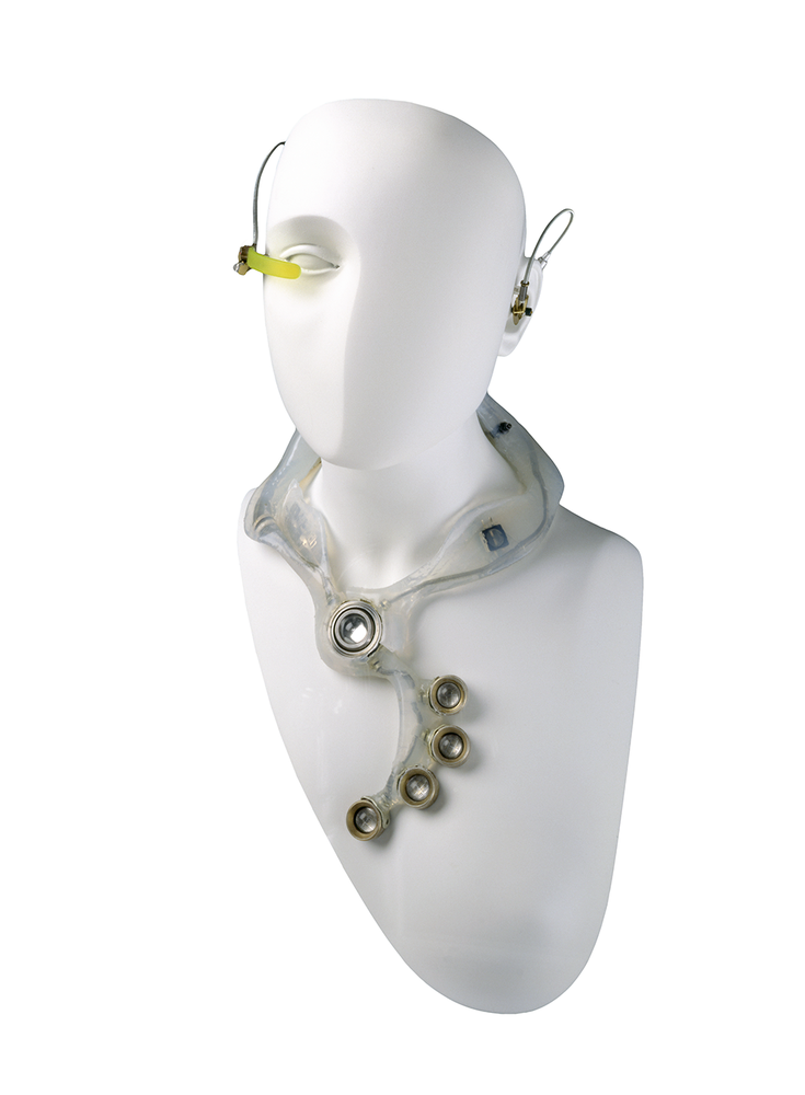 A white mannequin wearing a futuristic wired earpiece and necklace