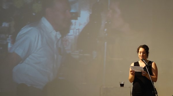 A woman speaks in front of a projected film