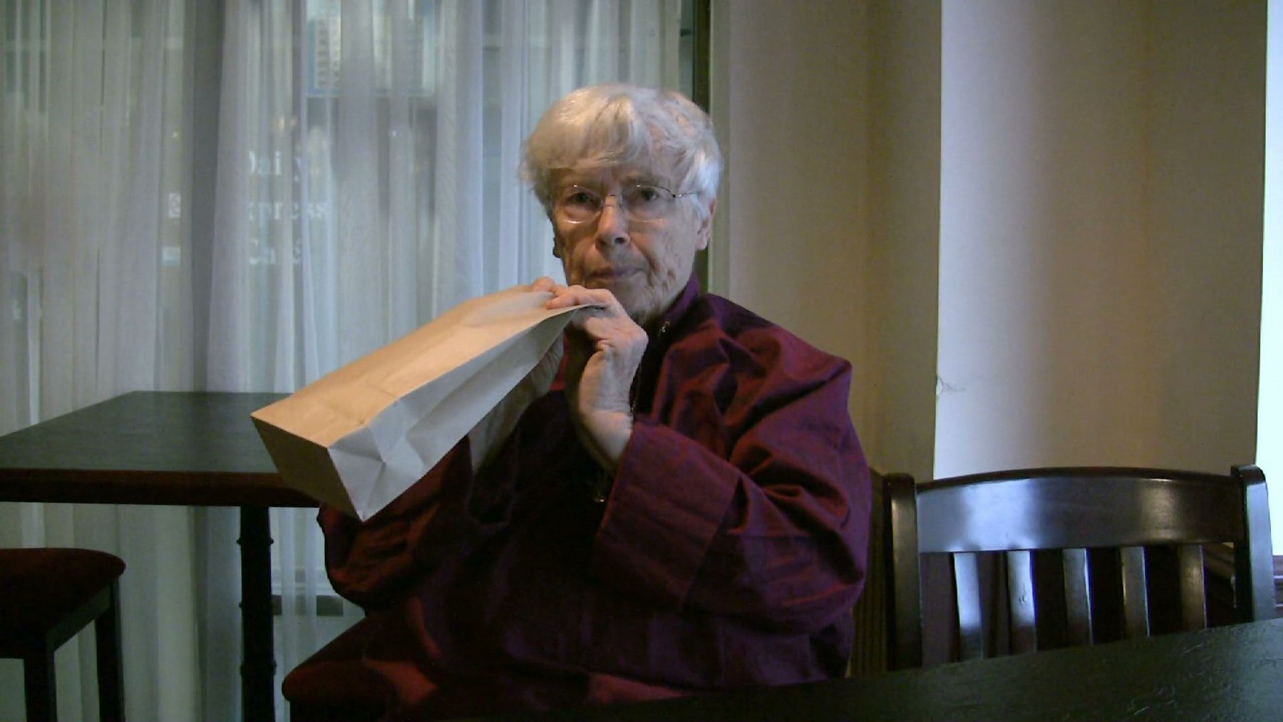 An elderly Caucasian woman with white hair holds a paper bag to her face, Lozano-Hemmer Soundtracks