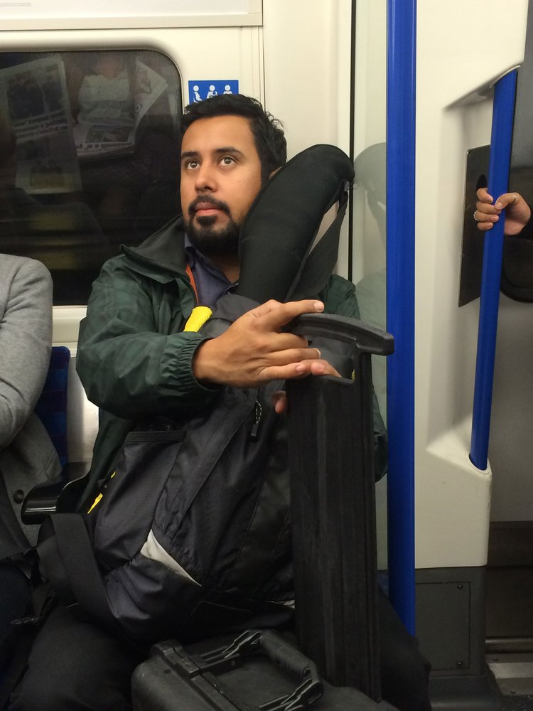 A bearded  man sitting on a subway, holding a huge equipment bag