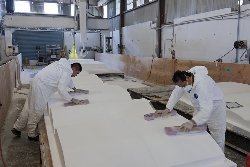 Workers in white suits carving a white undulating panel