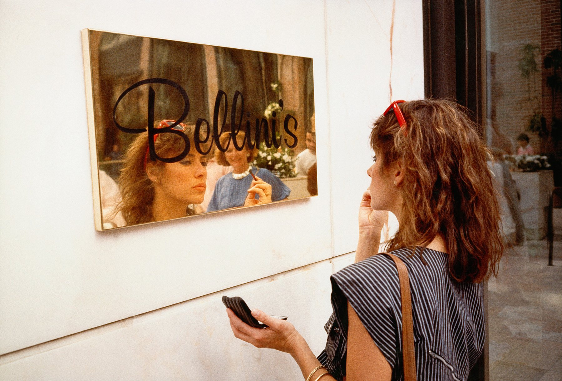 A woman looks into a relective store sign to fix her makeup