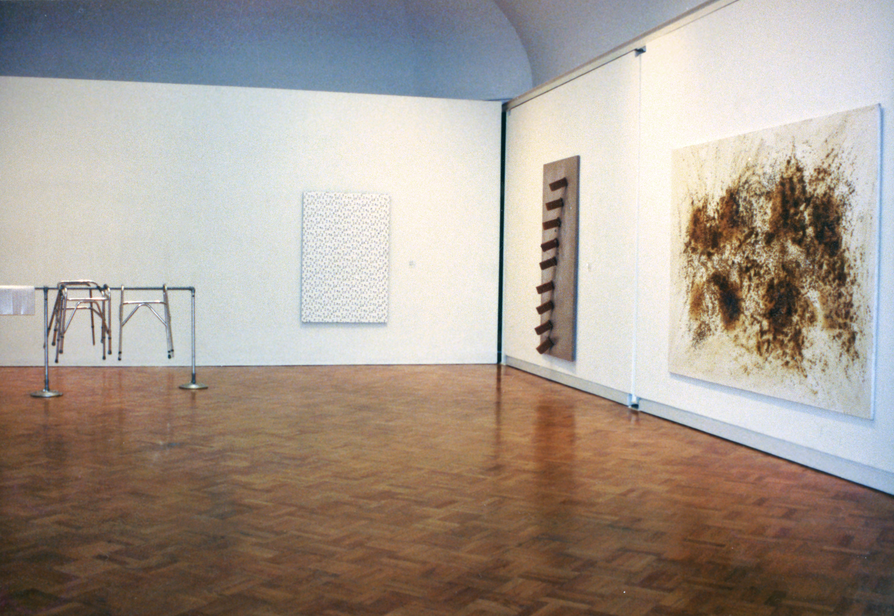 A gallery with one painting featuring dark brown smudges, a hanging steel sculpture with protruding cylinders, a hanging white artwork with a black pattern on it, and steel bars with steel furniture hanging on them.