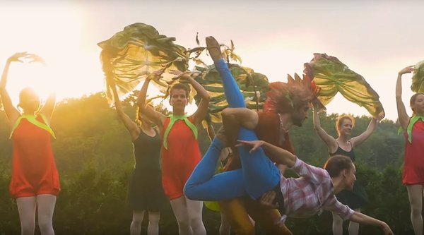 A group of dancers in colorful costumes perform outdoors