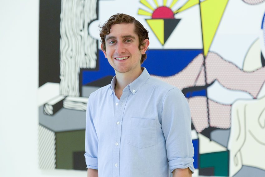 Portrait of a young Cuacasian man with curly brown hair in front of a colorful abstract artwork