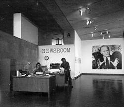 "A black and white photograph of a room with the words ""Newsroom"" printed on the wall"