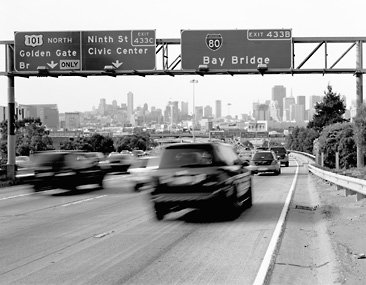 moving cars on highway under bay bridge sign