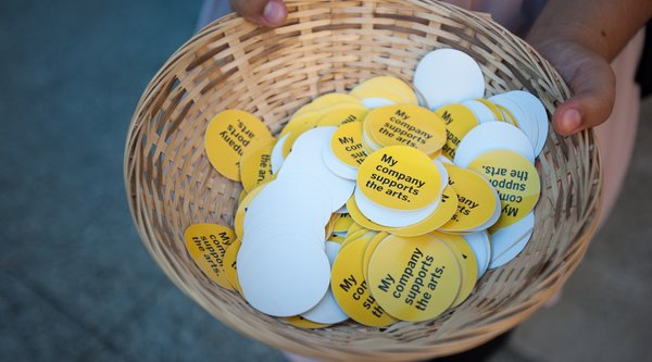 "A basket of stickers reading ""My organization supports the arts."""