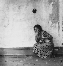 Woodman; photo of woman in polka dot dress leaning against decrepit wall