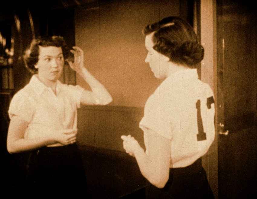 A Caucasian woman with short brown hair looks at herself in the mirror