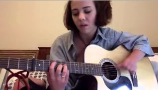 A girl sits on a bed and plays guitar
