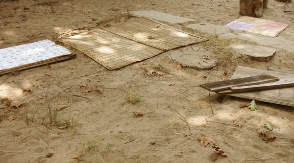 A photograph of a woven mat, plywood, and cement block lined up over an expanse of sand