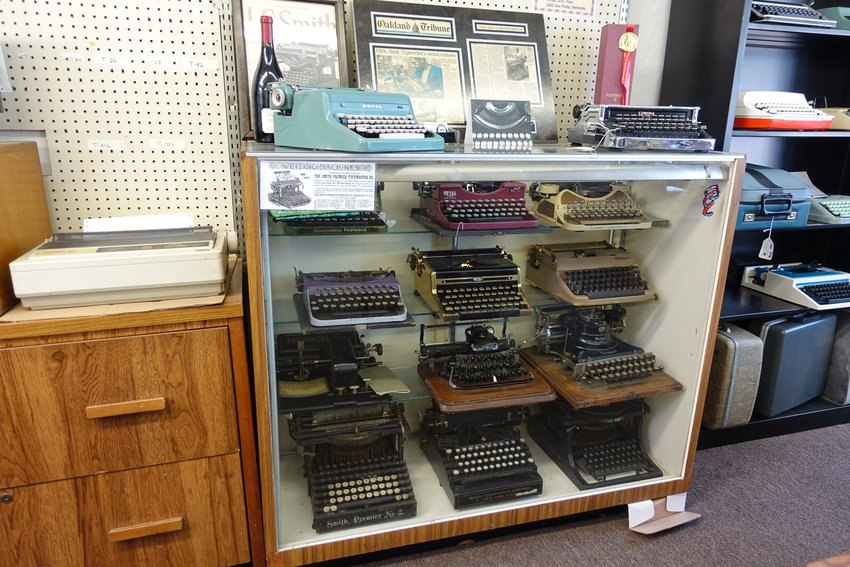 A shelf containing several antique and vintage typewriters