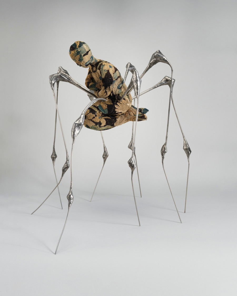 A sculpture with sliver legs and a fabric body shaped like a kneeling human