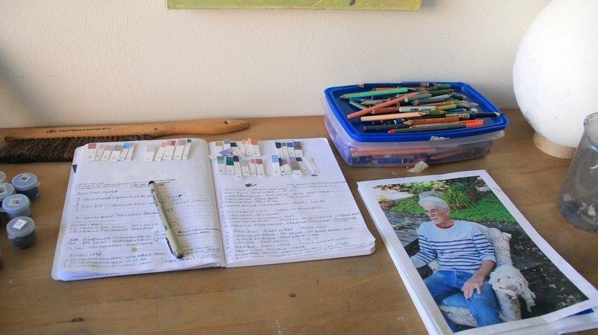 A desk containing an open notebook along side a photograph of an elderly Caucasian man wearing a striped shirt, Collinson