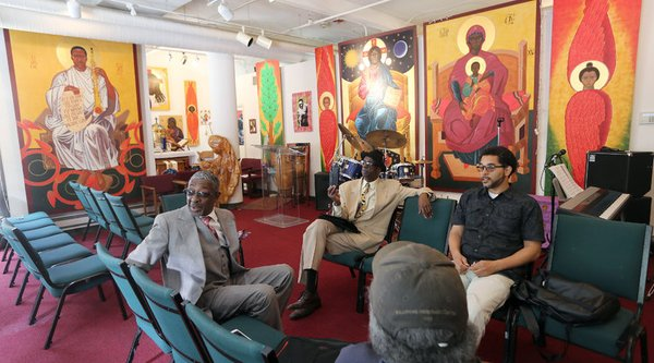 Three African American men sit in a gallery space filled with colorful paintings