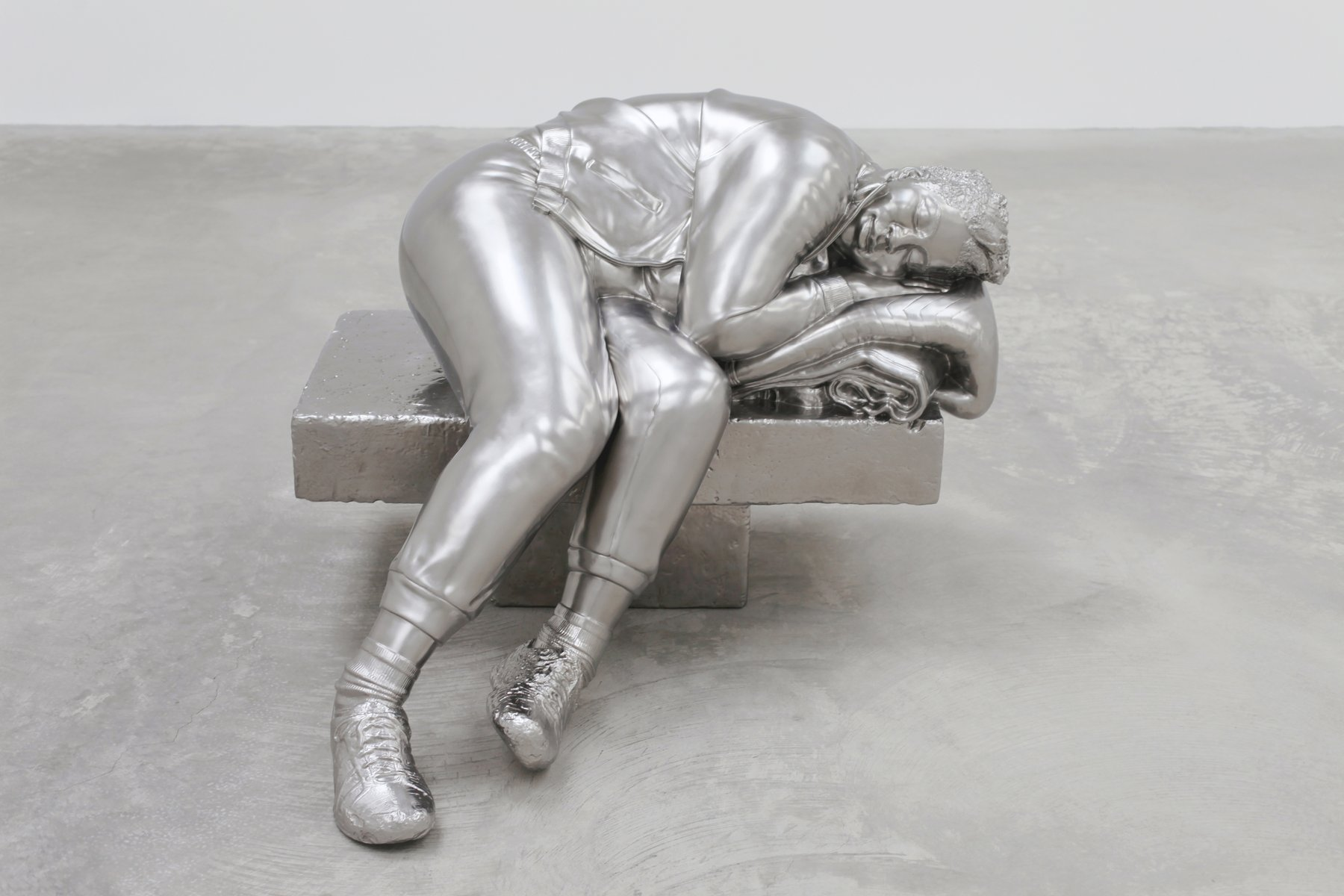 A silver sculpture of a woman sleeping on a bench.