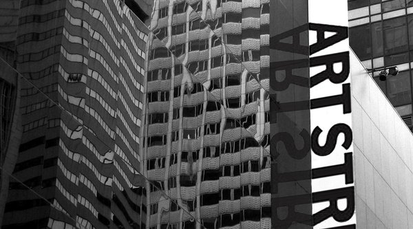 "A black and white photograph of a building with a banner saying ""art strike"" running down its side"