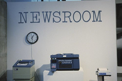 A white wall with the words Newsroom printed on it